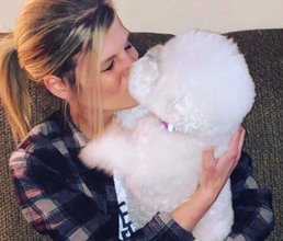 Team member Paige giving her dog a kiss